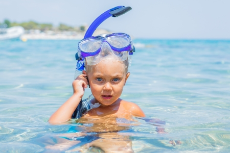 snorkling: Portrait of young boy in snorkling equipment swimming in the transparent sea Stock Photo