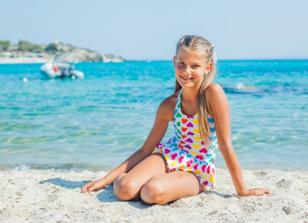 Cute happy girl sitting on the sand beach photo