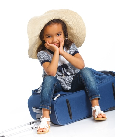 The young mulatto traveler girl with hat and a suitcase  Isolated over white background  Vertical view