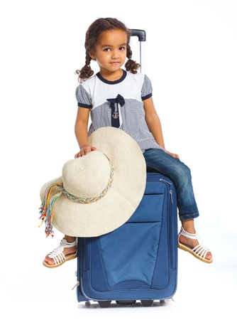 The young mulatto traveler girl with hat and a suitcase  Isolated over white background  Vertical view photo