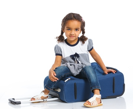 The young mulatto traveler girl with a suitcase  Isolated over white background photo