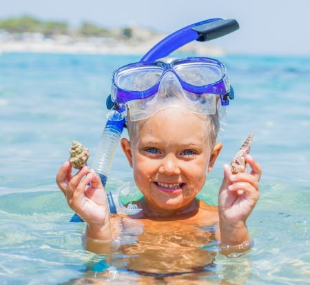 snorkling: Portrait of young boy with seashells in snorkling equipment swimming in the transparent sea