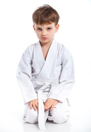 jujitsu: Aikido boy recreation position in white kimono isolated on white Stock Photo