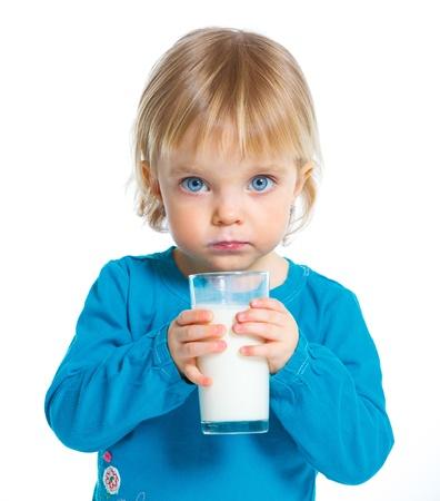 白い背景の上のミルクのガラスを持つ少女