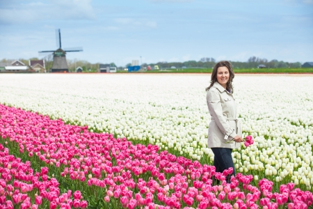 Young woman with bouquet between of the white-purple tulips field photo