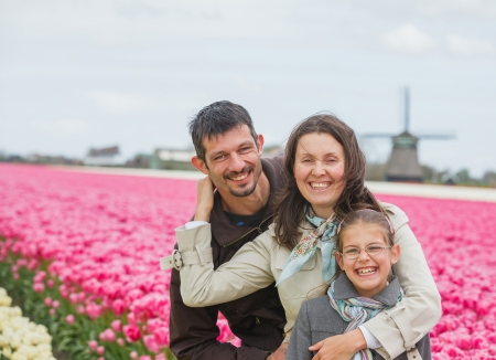 Family of three walks between of the purple and white tulips field Stock Photo - 18253936