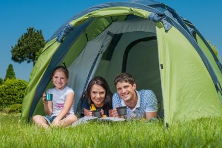 家族は草の上に休憩とテントとキャンプ 写真素材