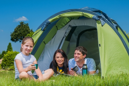 Families resting on the grass and camping with tent photo