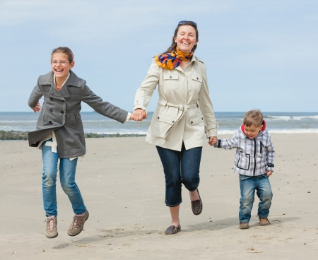 Cute young woman with two kids having fun on the Dutch beach Stock Photo - 18263093