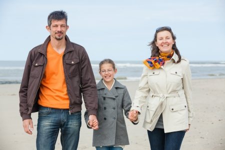 Beautiful family of three walking on the beach  Holland Stock Photo - 18268383