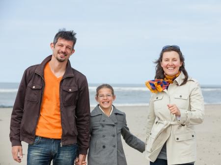 Beautiful family of three walking on the beach  Holland Stock Photo - 18268382