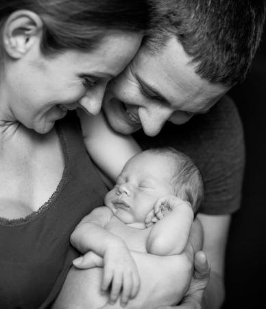美しい母と彼らの生まれたばかりの赤ちゃんの男の子を持って笑顔の父 写真素材