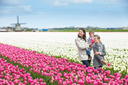 Mother with her child walks between of the purple tulips field Stock Photo - 18521829
