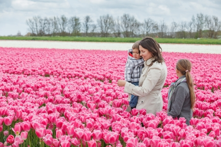 Mother with her child walks between of the purple tulips field Stock Photo - 18521833