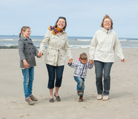 Cute young woman with two kids and grandmother having fun on the Dutch beach Stock Photo - 18521812