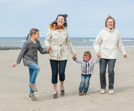 Cute young woman with two kids and grandmother having fun on the Dutch beach Stock Photo - 18521837