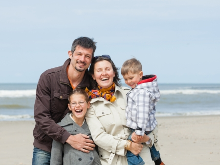Beautiful family of four walking on the beach  Holland Stock Photo - 18521825