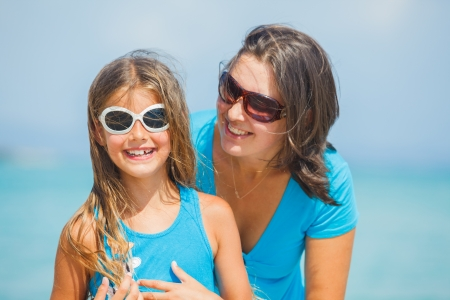 Portrait of mother and her daughter in sunglasses having fun on tropical beach photo