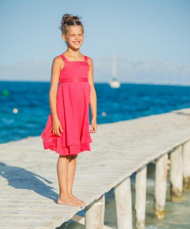 Cute beautiful girl walking on jetty with turquoise sea photo