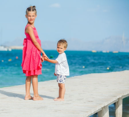 Cute toddler boy with his sister walking on jetty with turquoise sea photo