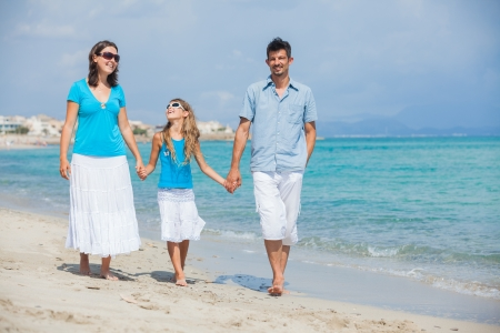 Happy family walking on the beach with little daughter photo