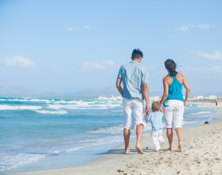 Back view of happy young family - mother, father and son having fun on the beach Stock Photo - 18542240