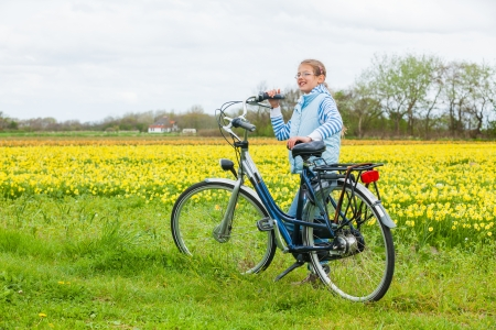 Young happy girl with bicycle standing in a field of daffodils photo