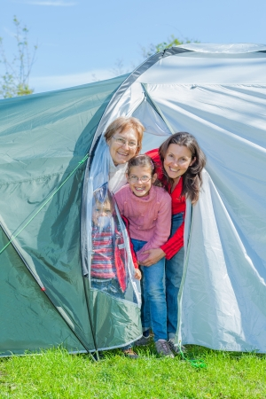 Family outdoor portrait of smiling mother, two kids and grandmother in tent in the camping on summer day photo