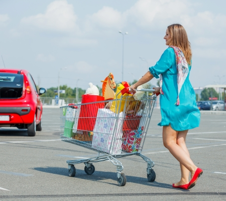 Beautiful pregnant woman with full handcart near a supermarket Stock Photo - 18577729