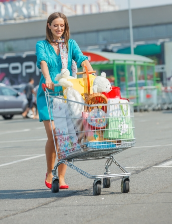 Beautiful pregnant woman with full handcart near a supermarket Stock Photo - 18577716