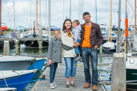 glad: Young happy family of four rests on Yacht Club and is glad at life  Stock Photo