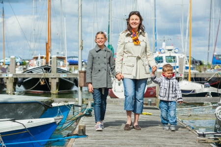 Young happy family of three rests on Yacht Club and is glad at life  Stock Photo - 18662012