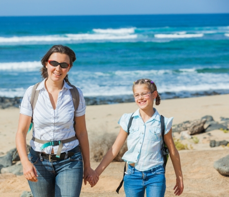 Mother with her daughter walking on a beach, wearing jeans and white shirts photo