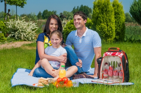 family outing: Caucasian happy family - mother, father and daughter having picnic in park  Stock Photo