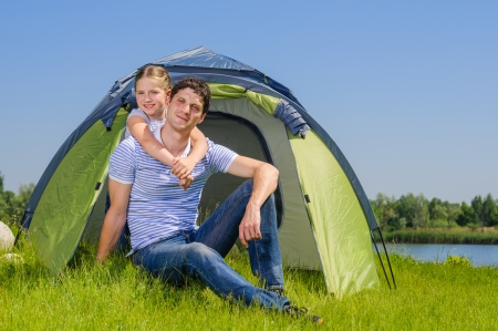 Father with his daughter resting on the grass and camping with tent photo