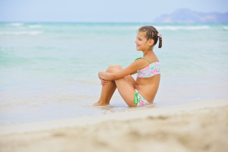 Adorable happy little smiling fun girl on beach vacation photo