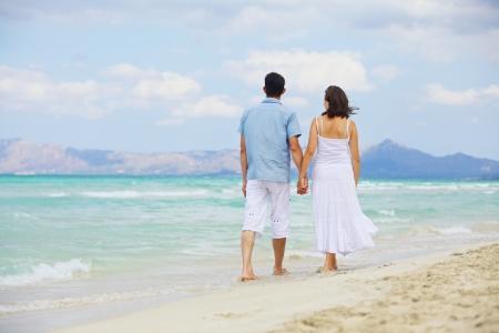 ビーチで楽しんで幸せな美しいカップルの肖像画
