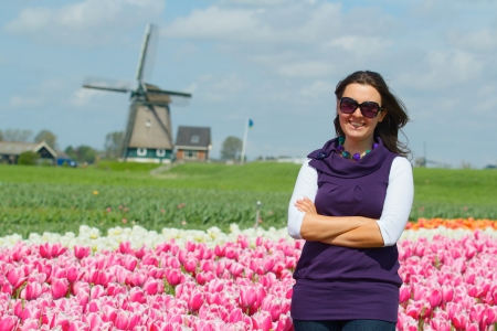 Young woman walking between of the white-purple tulips field photo