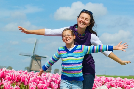 Cute girl and her mother between of the purple and white tulips field photo