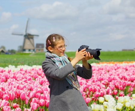 Cute girl is taking pictures in field with tulips in Holland  Stock Photo - 18871861