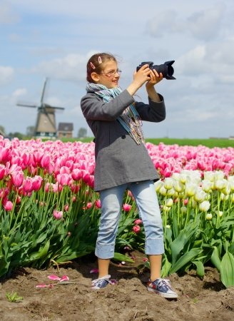 Cute girl is taking pictures in field with tulips in Holland  Vertical view photo