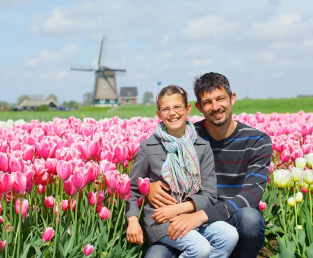 Cute girl and his father between of the purple tulips field photo