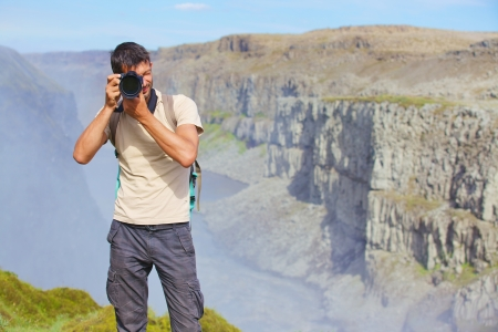 View of woman photographer standing near famous Dettifoss waterfall in Vatnajokull National Park, Northeast Iceland