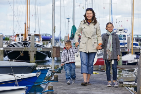 Young happy family of three rests on Yacht Club and is glad at life Stock Photo - 18989428