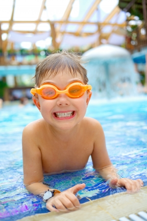 Activities on the pool  Cute boy swimming and playing in water in swimming pool photo
