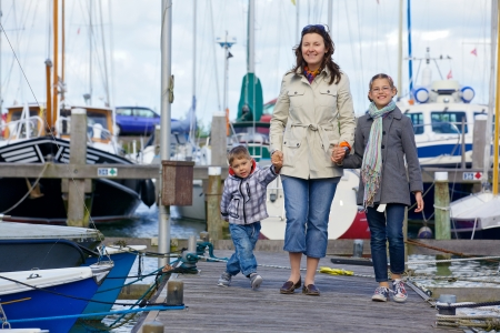 Young happy family of three rests on Yacht Club and is glad at life  photo