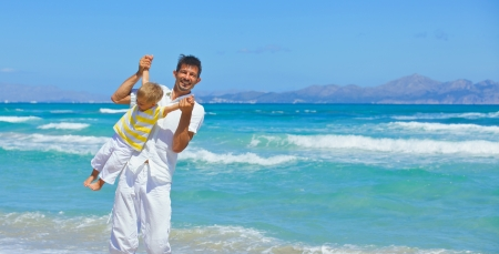 Father and son having fun on tropical white sand beach photo