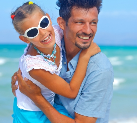 Closeup portrait of father with daughter having fun on tropical beach photo
