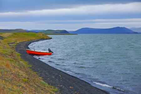 Iceland landscape with red boat on Myvatn lake in northern Iceland photo