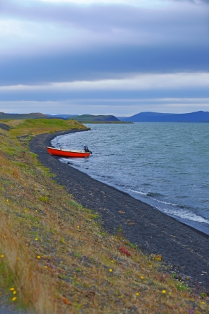 Iceland landscape with red boat on Myvatn lake in northern Iceland  Vertical view photo